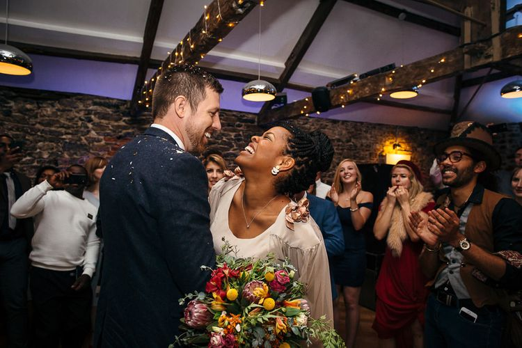 First Dance | Bride in Bespoke Ailsa Monroe Jumpsuit & Cape | Groom in Next Navy Wool Suit | Relaxed Industrial Wedding at Ocean Studios, Plymouth | Freckle Photography