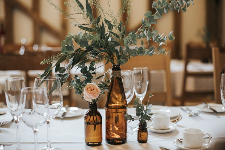 Brown Bottle & Flower Stem Centrepieces | Rustic Barn Wedding Reception at Gate Street Barn, Surrey | Kirsty MacKenzie Photography