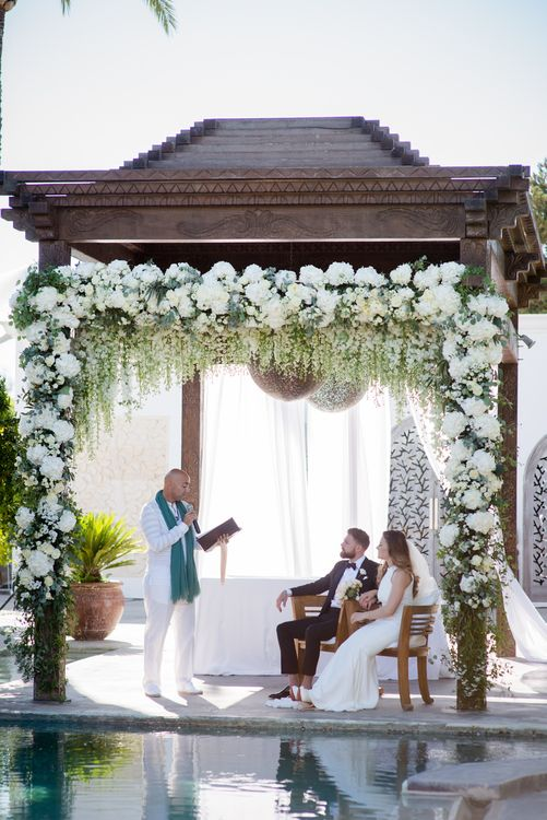Flower Covered Arbour | Bride in Suzanne Neville Wedding Dress | Groom in Reiss Suit | Outdoor Ibiza Destination Wedding | Gypsy Westwood Photography | Infin8 Film