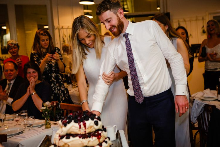 Cutting the Cake | Bride in Pleats Please Issey Miyak Dress | Groom in Beggars Run Suit | Chic London Wedding at St Bartholomew the Great Church & St John Bar & Restaurant | Helen Abraham Photography