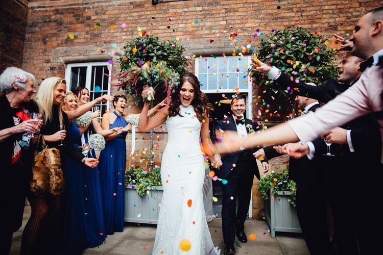 Confetti Exit | Bride in Pronovias Ornani Bridal Gown & Veil | Groom in Charles Tyrwitt Midnight Blue Tuxedo | Industrial Wedding at The West Mill Venue | Sarah Gray Photography