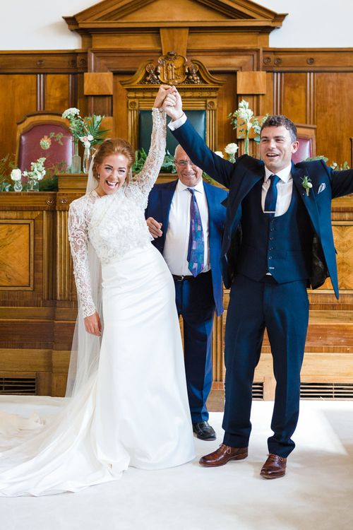 Wedding Ceremony | Bride in Bespoke Emma Beaumont Gown | Groom in Navy Suit | Greenery, White & Gold Stylish Wedding at The Town Hall Hotel in London | Lucy Davenport Photography