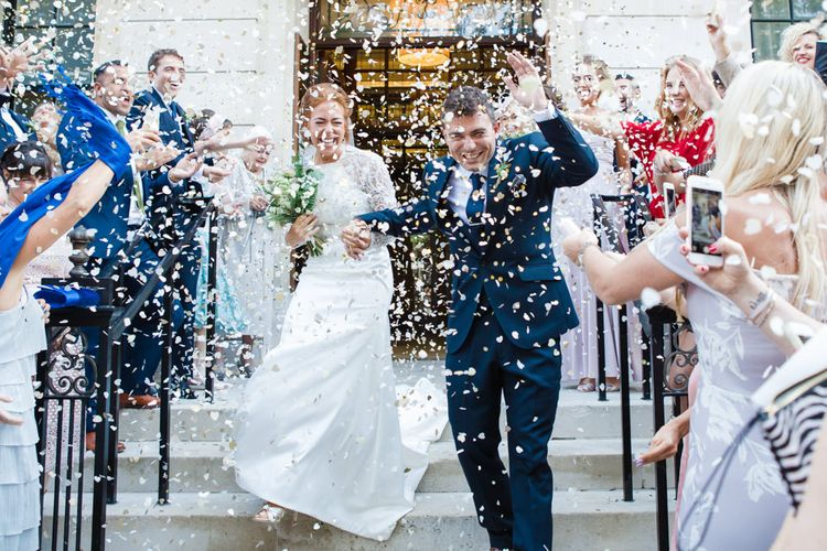 Confetti Exit | Bride in Bespoke Emma Beaumont Gown | Groom in Navy Suit | Greenery, White & Gold Stylish Wedding at The Town Hall Hotel in London | Lucy Davenport Photography