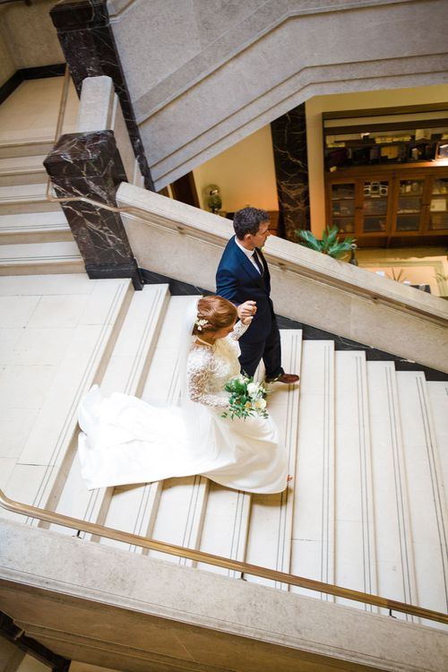 Bride in Bespoke Emma Beaumont Gown | Groom in Navy Suit | Greenery, White & Gold Stylish Wedding at The Town Hall Hotel in London | Lucy Davenport Photography
