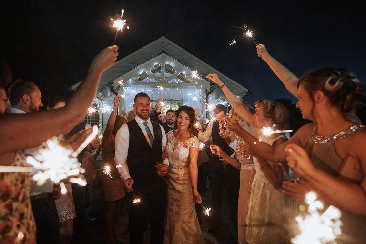 Sparkler Exit   Bride in Justin Alexander Gown   Groom in Blue Check Hugo Boss Suit   White & Green Reception at The Red Barn, Kent with Balloon Decor   Olegs Samsonovs Photography