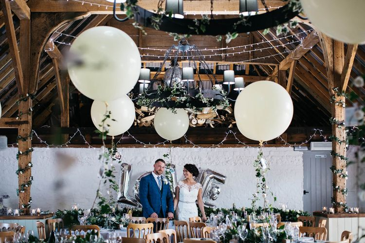 Bride in Justin Alexander Gown   Groom in Blue Check Hugo Boss Suit   White & Green Reception at The Red Barn, Kent with Balloon Decor   Olegs Samsonovs Photography