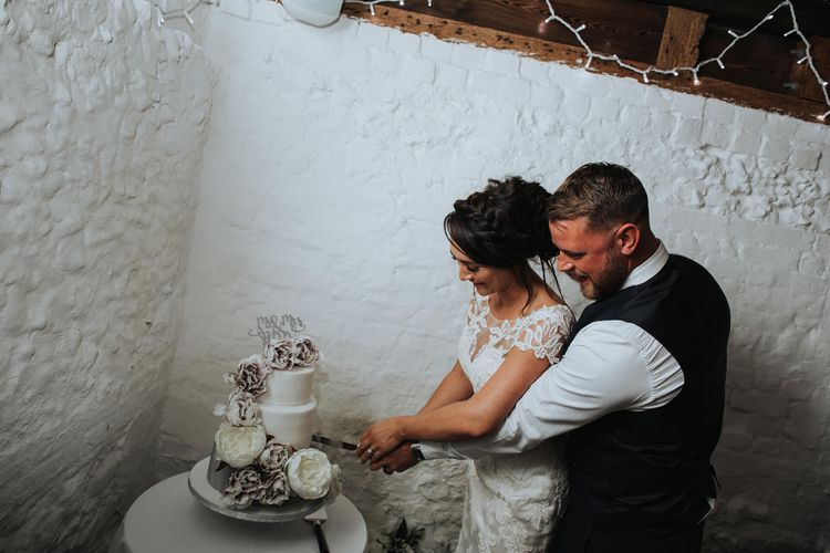 Cutting the Cake   Bride in Justin Alexander Gown   Groom in Blue Check Hugo Boss Suit   White & Green Reception at The Red Barn, Kent with Balloon Decor   Olegs Samsonovs Photography