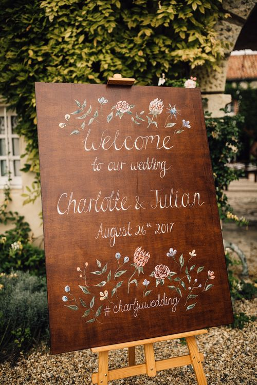 Hand Painted Wooden Welcome Sign | Outdoor Destination Wedding at Château De Malliac Planned by Country Weddings in France | Styling by The Hand-Painted Bride | Samuel Docker Photography | Marriage in Motion Films