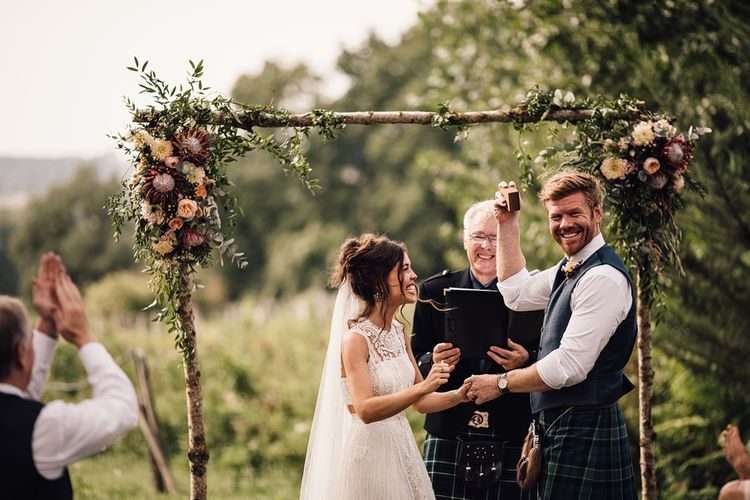 Wedding Ceremony | Floral Altar | Bride in Lace Yolan Cris Gown | Groom in Tartan Kilt | Outdoor Destination Wedding at Château De Malliac Planned by Country Weddings in France | Styling by The Hand-Painted Bride | Samuel Docker Photography | Marriage in Motion Films