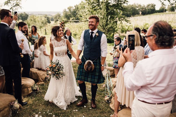 Wedding Ceremony | Bride in Lace Yolan Cris Gown | Groom in Tartan Kilt | Outdoor Destination Wedding at Château De Malliac Planned by Country Weddings in France | Styling by The Hand-Painted Bride | Samuel Docker Photography | Marriage in Motion Films