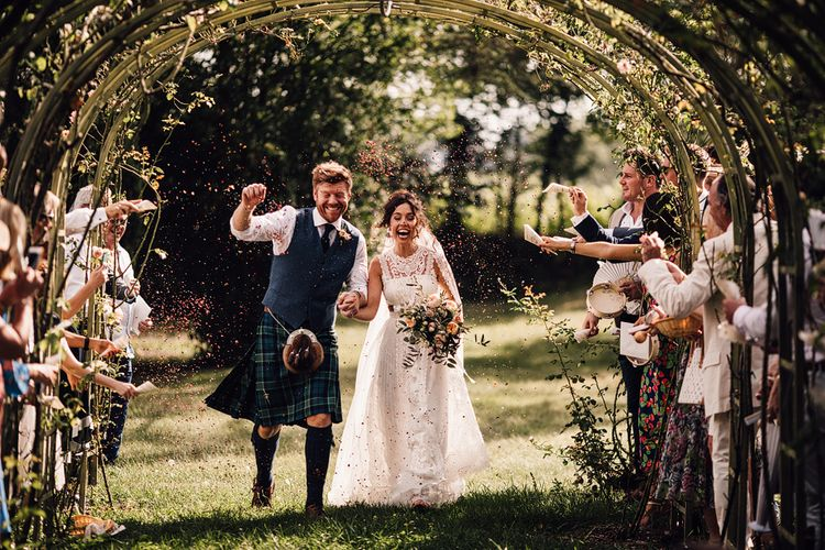 Confetti Exit | Bride in Lace Yolan Cris Gown | Groom in Tartan Kilt | Outdoor Destination Wedding at Château De Malliac Planned by Country Weddings in France | Styling by The Hand-Painted Bride | Samuel Docker Photography | Marriage in Motion Films
