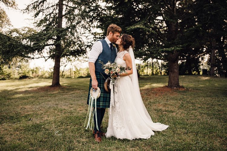 Bride in Lace Yolan Cris Gown | Groom in Tartan Kilt | Outdoor Destination Wedding at Château De Malliac Planned by Country Weddings in France | Styling by The Hand-Painted Bride | Samuel Docker Photography | Marriage in Motion Films