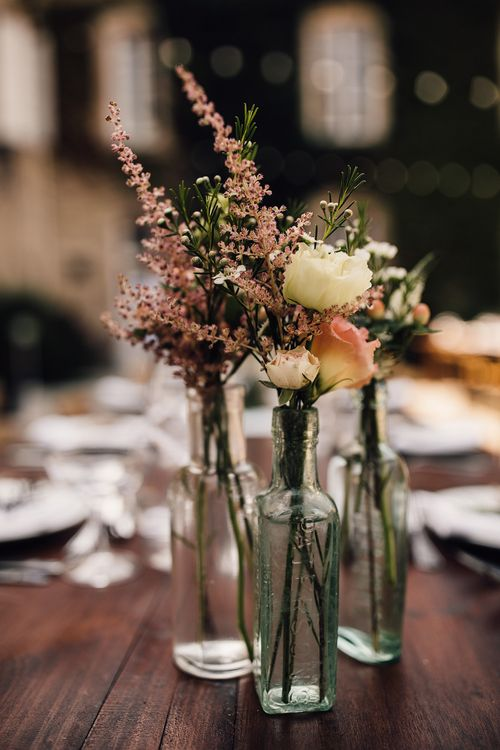 Flower Stems in Bottles Wedding Decor | Outdoor Destination Wedding at Château De Malliac Planned by Country Weddings in France | Styling by The Hand-Painted Bride | Samuel Docker Photography | Marriage in Motion Films