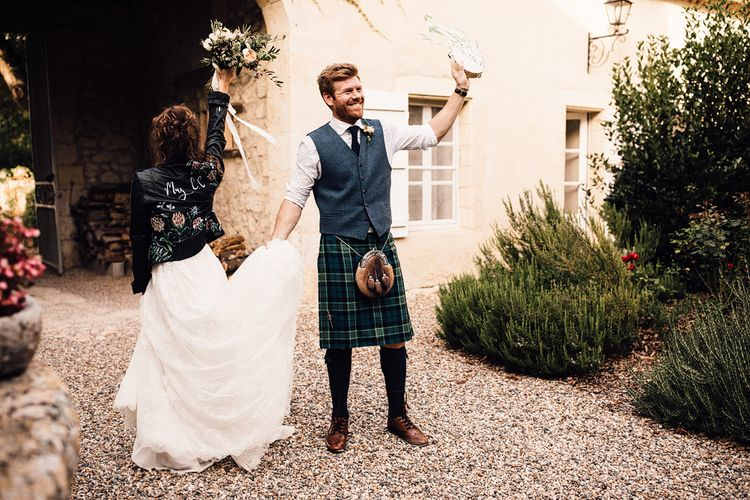 Bride in Yolan Cris Lace Gown & Leather Jacket | Groom in Tartan Kilt | Outdoor Destination Wedding at Château De Malliac Planned by Country Weddings in France | Styling by The Hand-Painted Bride | Samuel Docker Photography | Marriage in Motion Films