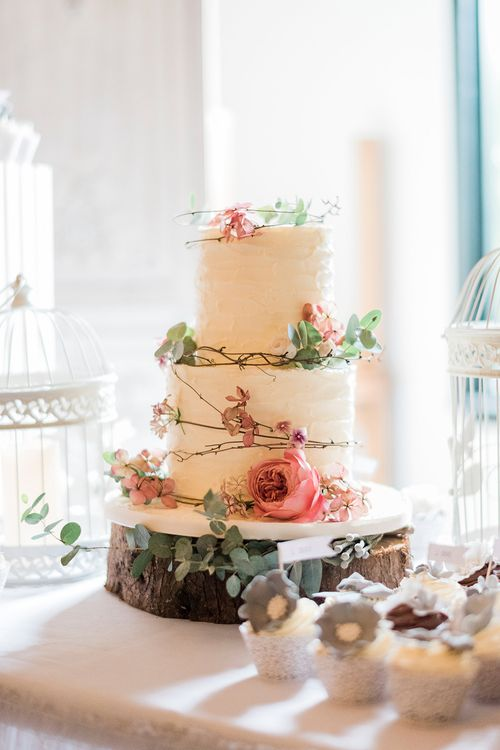 Iced Wedding Cake & Coral Decor on Tree Stump Cake Stand | Romantic Peach & Coral Floral Centrepiece | Peach & Coral Country Wedding at Crabbs Barn, Essex | Kathryn Hopkins Photography | Film by Colbridge Media Services Ltd