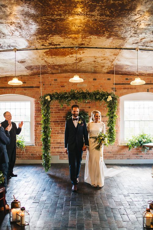Bride in Charlie Brear Torum Dress & Adrianna Lace Jacket | Industrial Wedding Ceremony at The West Mill | Greenery Flower Arch | S6 Photography