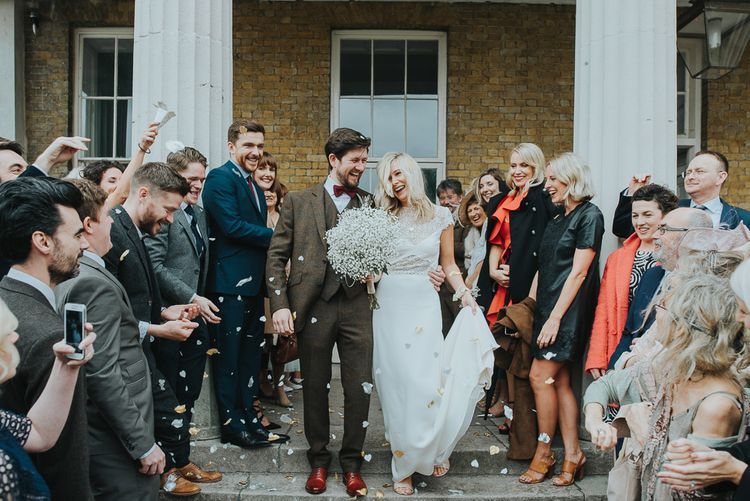 Confetti Moment with Bride in Anais Anette Savannah Bridal Gown & Groom in Walker Slater Tweed Suit
