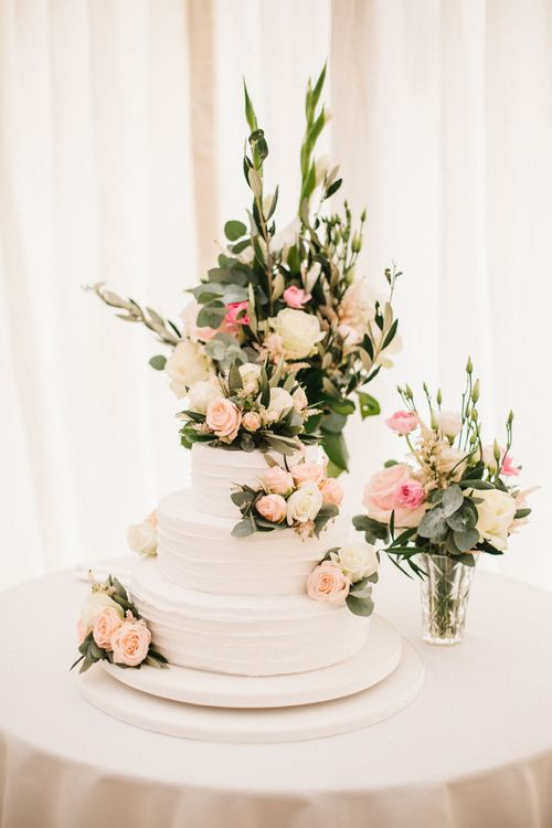 White Wedding Cake Covered In Flowers