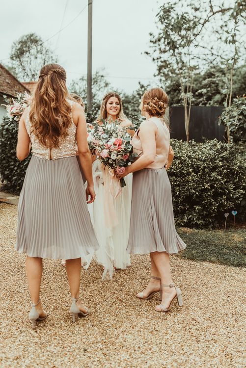 Bridesmaid in Pleated TFNC Skirts with different tops | DIY At Home Marquee Reception | Jess Soper Photography