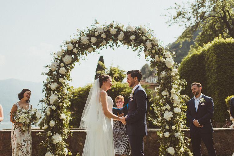 Floral Arch | Wedding Ceremony | Bride in Karen Willis Holmes Gown | Groom in Navy Peter Jackson Suit | Outdoor Destination Wedding at Villa Regina Teodolinda, Lake Como, Italy | Matt Penberthy Photography