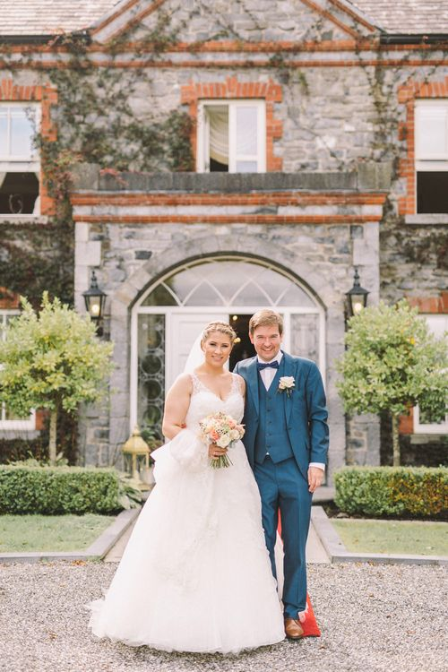 Bride in Modeca Wedding Dress & Groom in Navy Three Piece Suit