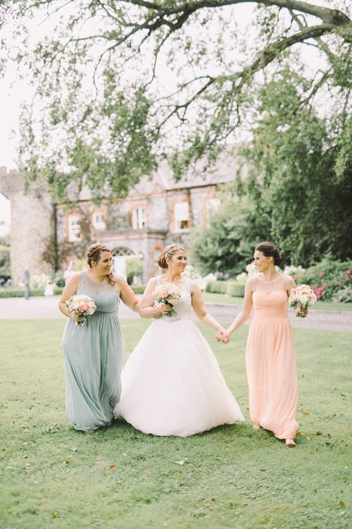 Bride in Modeca Wedding Dress & Bridesmaids in Pastel Peach & Green Gowns