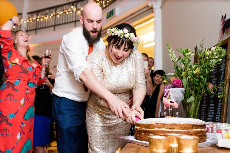 Cutting the Cake with Bride in Pre Owned Gold Sequin Badgley Mischka Wedding Dress & Groom in Suit Supply