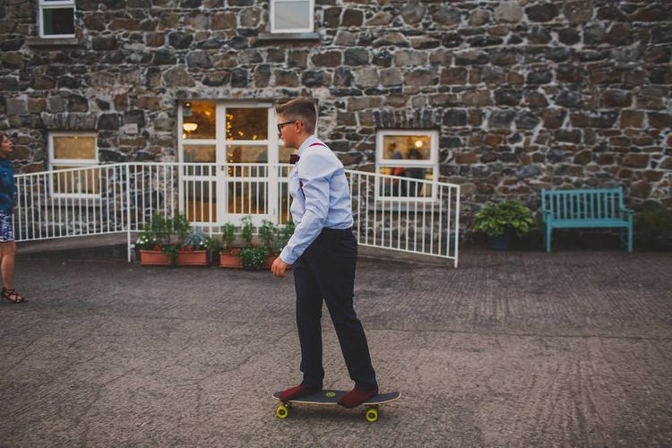 Young Wedding Guest on Skateboard   Navyblur Photography   Cinematic Tide Films