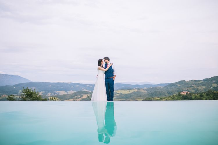 Bride in Naomi Neoh Gown & Groom in French Connection Suit near Pool