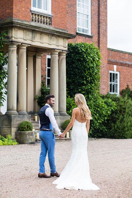 Bride in Pronovias Wedding Dress & Groom in Blue Hugo Boss Suit Outside Iscoyd Park in Shropshire