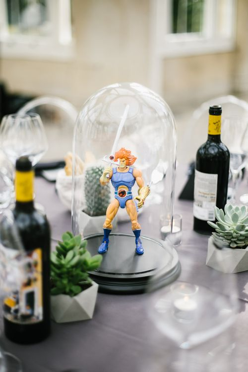 Iconic 80s Figure (Lion-o Thundercat) in Bell Jar Table Centrepiece Wedding Decor | Monochrome Wedding at Syon Park London | Chris Barber Photography | Second Shooter Beatrici Photography