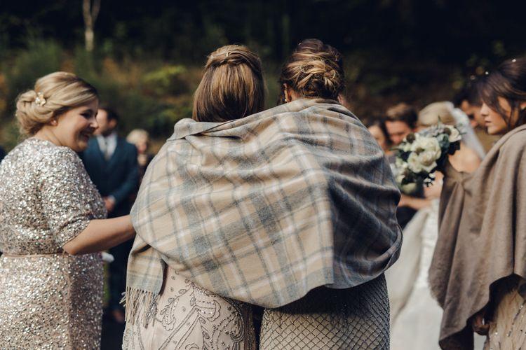 Bridesmaids Keep Warm Under Blanket