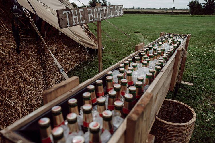 Wooden Trough Bottle Bar   Rustic At Home Tipi Reception with Blush Colour Scheme   Jason Mark Harris Photography   Harris Films