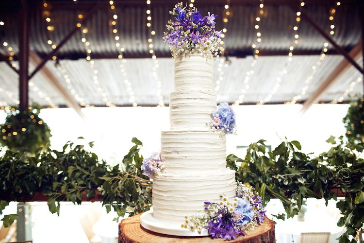 White Buttercream Wedding Cake With Purple Flowers