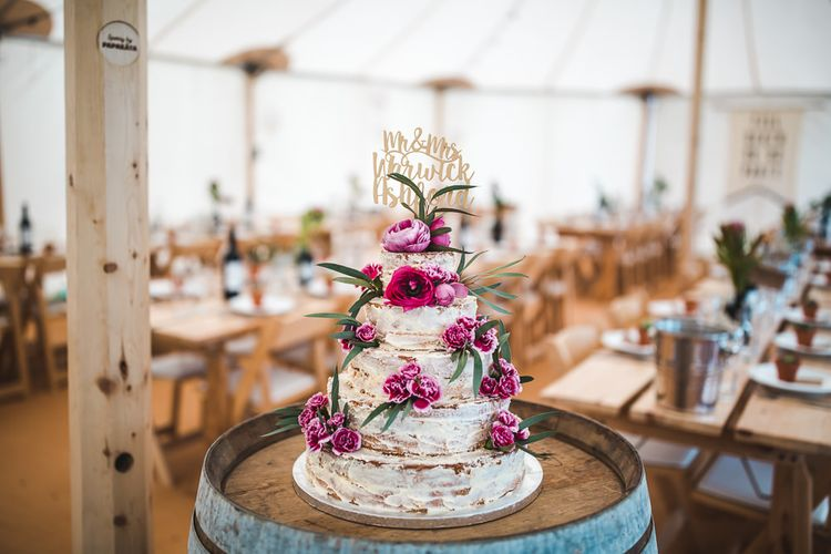 Semi Naked Wedding Cake on a Barrel with Flower Decor | PapaKåta Sperry Tent at Chafford Park in Kent Countryside | Eve Dunlop Photography | Roost Film Co.