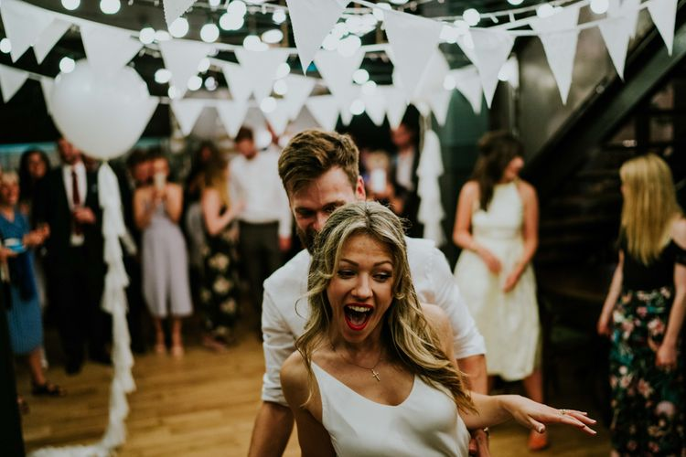 First Dance under White Bunting | Bride in Bespoke Soon Bride Gown | Groom in Whisles Pale Blue Suit | Contemporary Wedding at the Artisan Bar Clerkenwell, London | Bridgwood Wedding Photography | Long Story Short Film