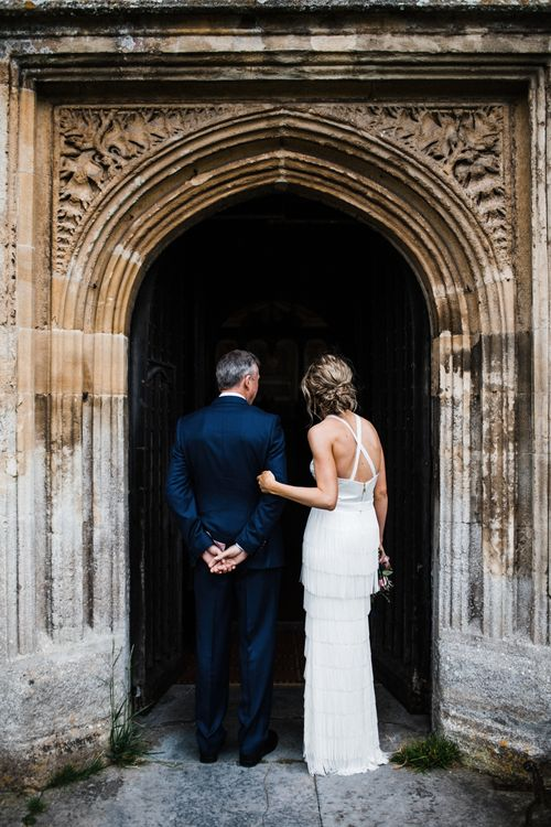 The Bride walks in to beautiful St Mary's Church in Burton, The Cotswolds. Image by Through the Woods We Ran.