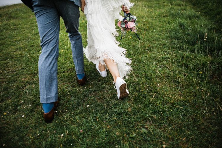 Bride witched her heels for white Converse for couple photo shoot in The Cotswolds after wedding. Image by Through the Woods We Ran.