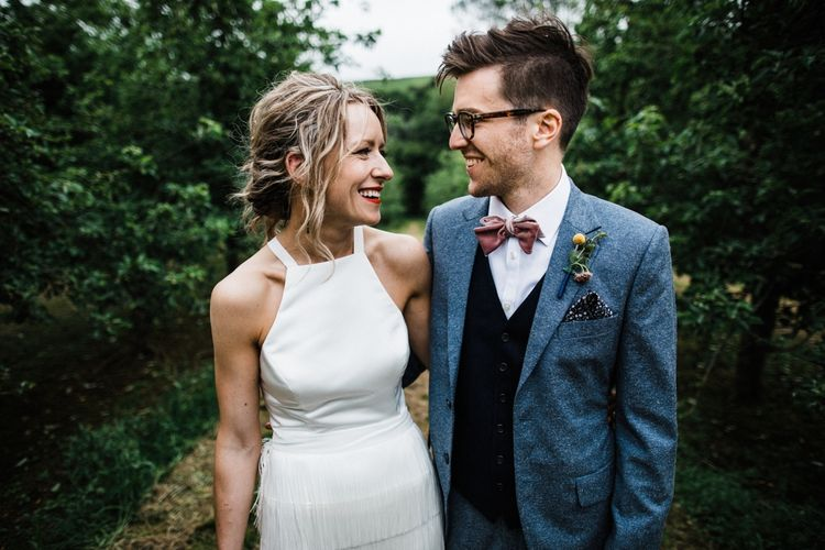 Bowtie by Mrs Bowtie. Bride in white Converse and Fringed skirt by Charlie Brear looking fabulous. Couple photo shoot in The Cotswolds after wedding. Image by Through the Woods We Ran.