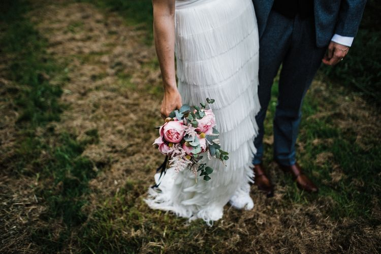 Stunning natural bouquet. Bride in white Converse and Fringed skirt by Charlie Brear looking fabulous. Couple photo shoot in The Cotswolds after wedding. Image by Through the Woods We Ran.