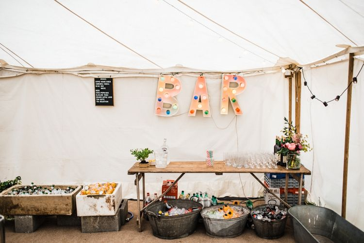DIY Wedding Bar. Ice Buckets, Festoon Letters and lots of Vodka. Image by Through the Woods We Ran.