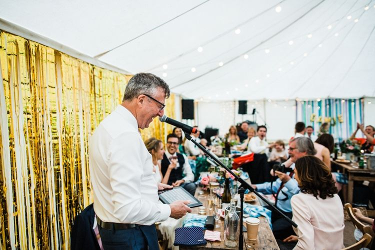 Wedding Toast with a beautiful gold DIY backdrop. Image by Through the Woods We Ran.