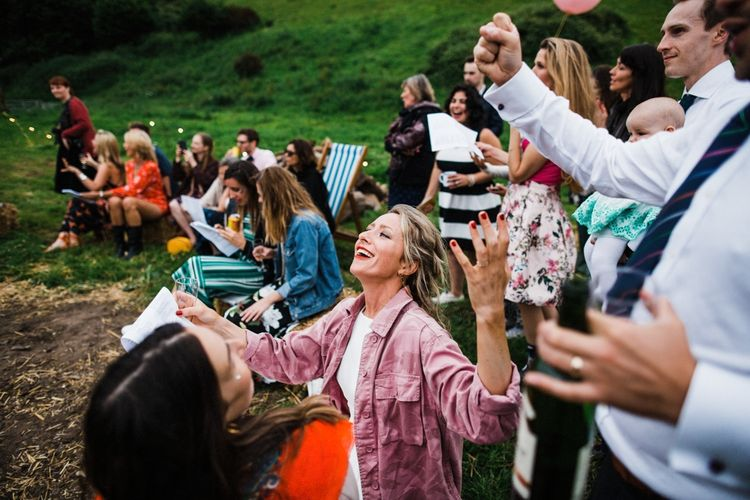 Bonfire singalong with Vodka and personalised bridal coat. Image by Through the Woods We Ran.