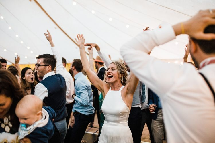 Dancing the night away with Spotify playlist at wedding. personalised bridal coat. Image by Through the Woods We Ran.