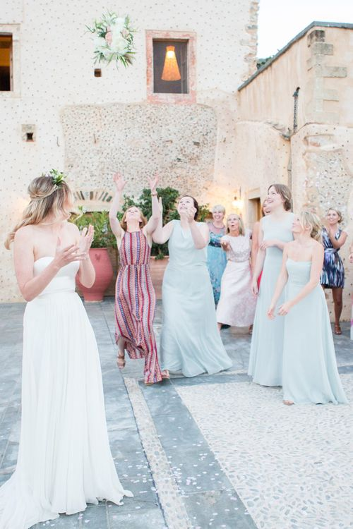 Wedding Bouquet Toss   Bride in BHLDN Gown   Intimate Outdoor Destination Wedding at Kinsterna Hotel & Spa in Greece   Cecelina Photography