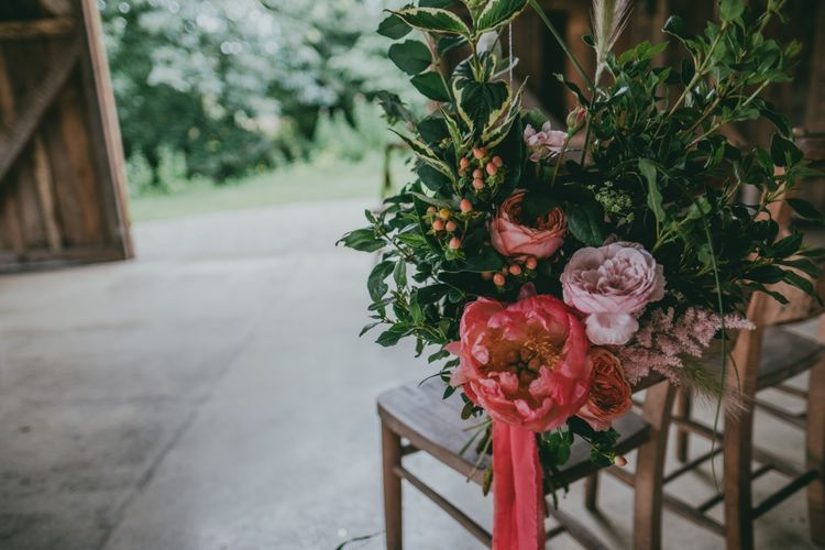 Coral Peony Chair Back Decor | Coral Wedding Cake with Peony Decor | Bride in Anna Campbell Gown from Coco & Kate Boutique | Groom in Next Wool Suit | Rustic Barn Pink Summer Wedding at Nancarrow Farm in Cornwall | Ross Talling Photography