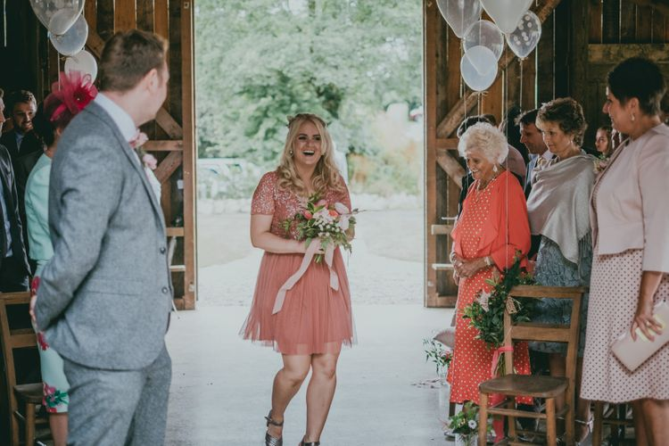 Wedding Ceremony | Bridesmaid Entrance | Coral Wedding Cake with Peony Decor | Bride in Anna Campbell Gown from Coco & Kate Boutique | Groom in Next Wool Suit | Rustic Barn Pink Summer Wedding at Nancarrow Farm in Cornwall | Ross Talling Photography