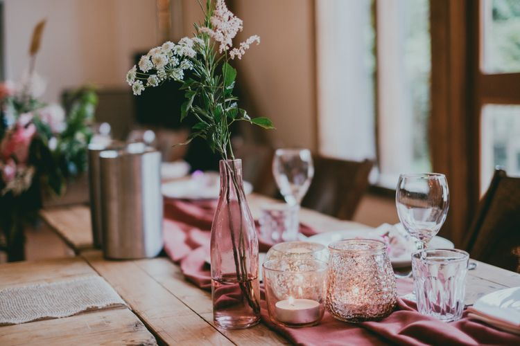 Pink Bottle with Flower Stem | Bride in Anna Campbell Gown from Coco & Kate Boutique | Groom in Next Wool Suit | Rustic Barn Pink Summer Wedding at Nancarrow Farm in Cornwall | Ross Talling Photography