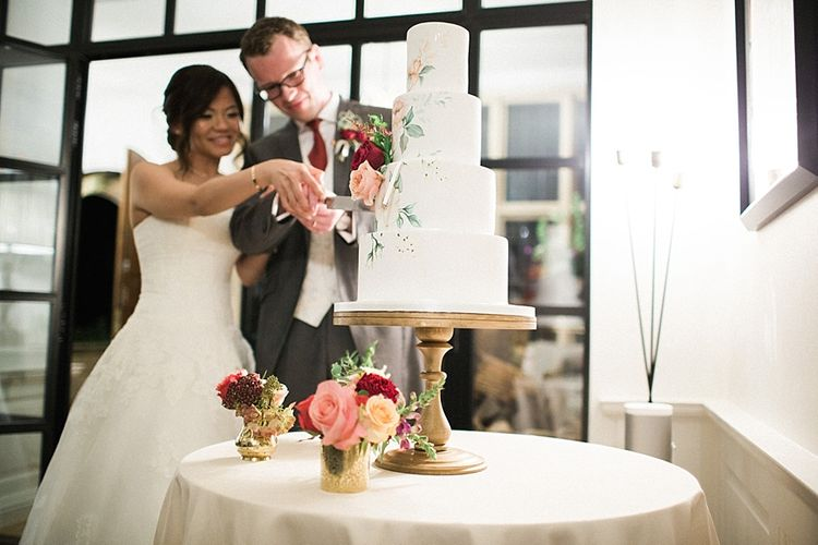 Cutting the Cake | Bride in Renee L. Collections Gown | Groom in Moss Bros Traditional Suit | Jacob & Pauline Photography | Pretty in White Films