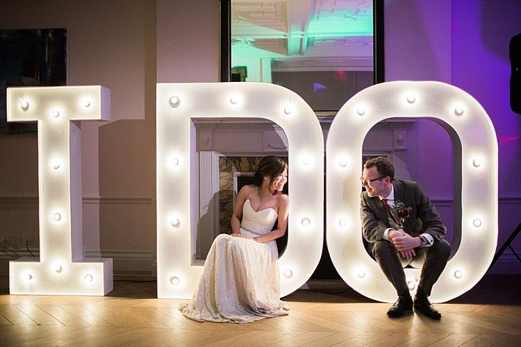 Vowed & Amazed I Do Giant Marquee Lights | Bride in Renee L. Collections Gown | Groom in Moss Bros Traditional Suit | Jacob & Pauline Photography | Pretty in White Films